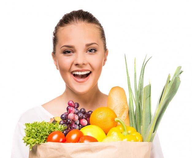 Mujer alegre que sostiene el bolso de compras lleno de comida fresca.