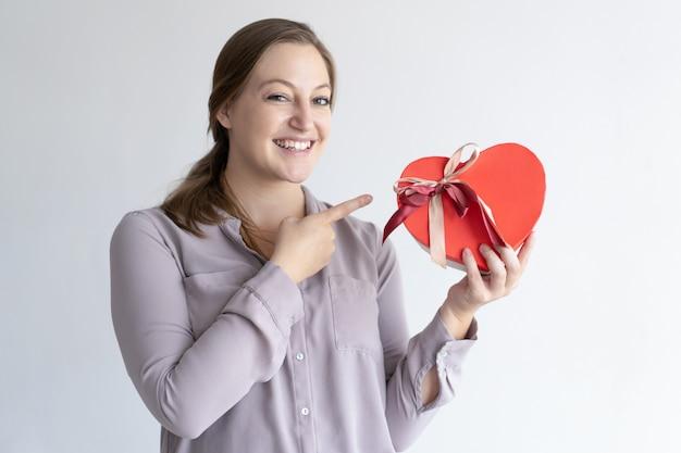Mujer alegre que sostiene la caja de regalo en forma de corazón y que señala en ella