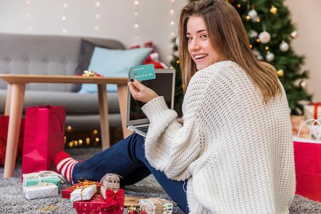 Mujer alegre que sostiene la tarjeta en los regalos de la navidad