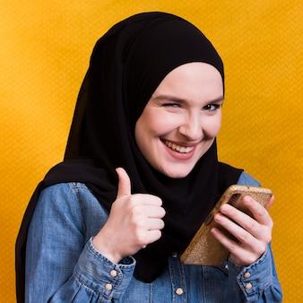 Mujer alegre que sostiene el teléfono móvil que gesticula el thumbup contra superficie amarilla