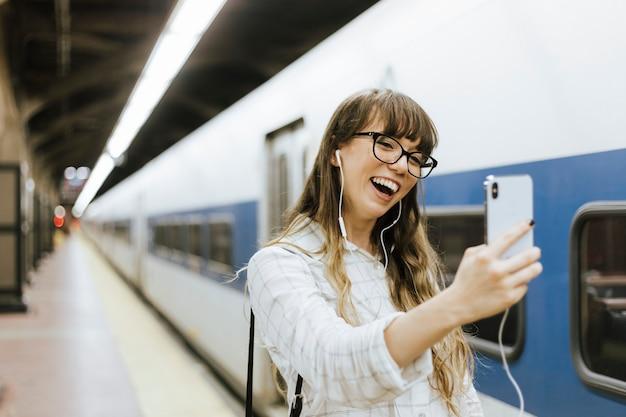 Mujer alegre que tiene una videollamada en una plataforma de metro