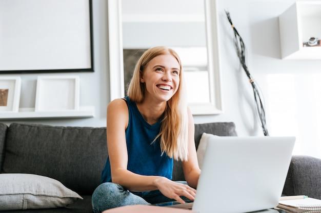 Mujer alegre que usa la computadora portátil y riéndose en casa