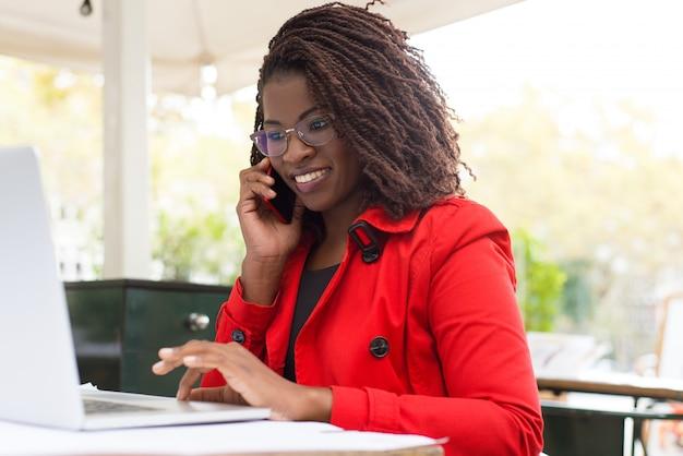 Mujer alegre que usa la computadora portátil y el teléfono inteligente