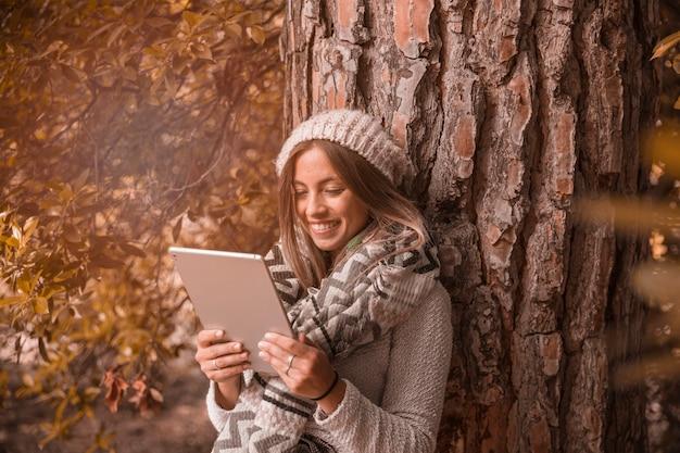 Mujer alegre que usa la tableta cerca del árbol
