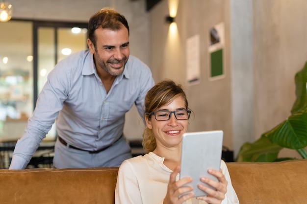 Mujer alegre que usa la tableta de la pc, su colega de pie detrás