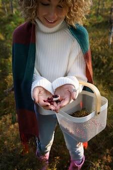 Mujer alegre recogiendo setas y arándanos en el bosque de otoño disfrutar de un clima cálido y ocio de otoño