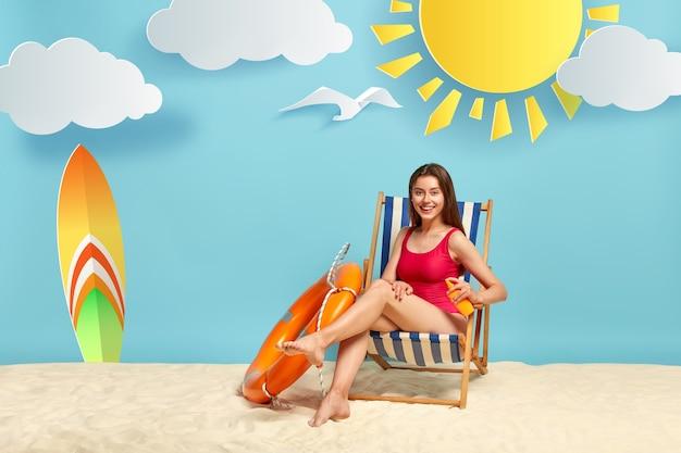 Mujer alegre y relajante aplica crema de protección solar en la pierna, posa en la playa en silla