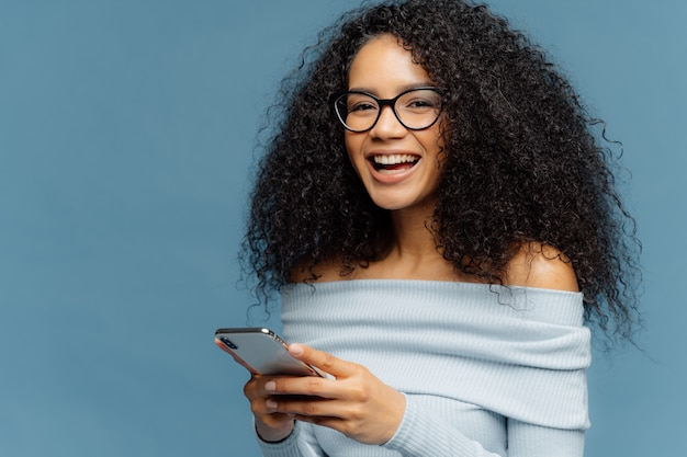 Mujer alegre rizada con expresión complacida, tiene teléfono móvil, revisa la casilla de correo electrónico