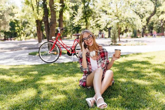 Mujer alegre en ropa de verano sentada en la hierba y tomando café. tiro al aire libre de fascinante chica con gafas hablando por teléfono sobre la naturaleza.