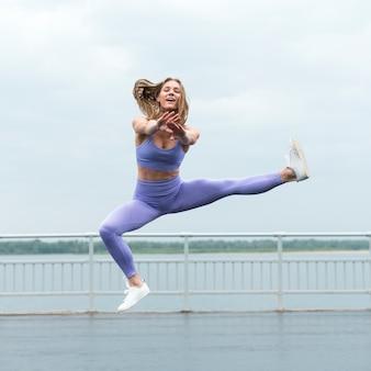 Mujer alegre saltando tiro largo