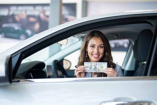 Mujer alegre sentada en el coche nuevo con billete de dólar estadounidense