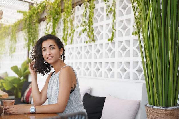 Mujer alegre sentada en la terraza de verano de café