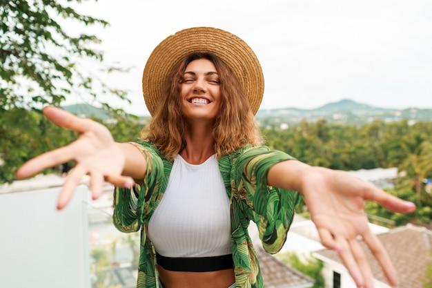 Mujer alegre con sombrero de paja, divirtiéndose, extiende las manos a la cámara.