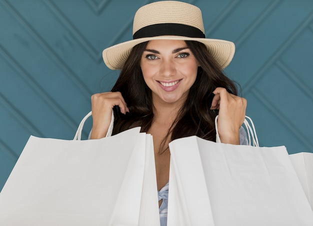 Mujer alegre con sombrero y redes comerciales