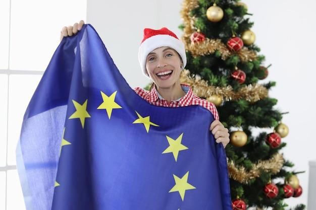 Mujer alegre con sombrero de santa claus sostiene la bandera de la unión europea contra el fondo del árbol de navidad