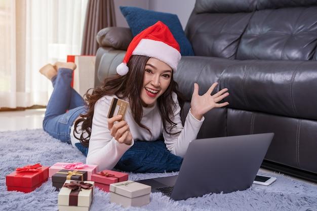 Mujer alegre en el sombrero de santa que hace compras en línea para el regalo de la navidad con el ordenador portátil en sala de estar