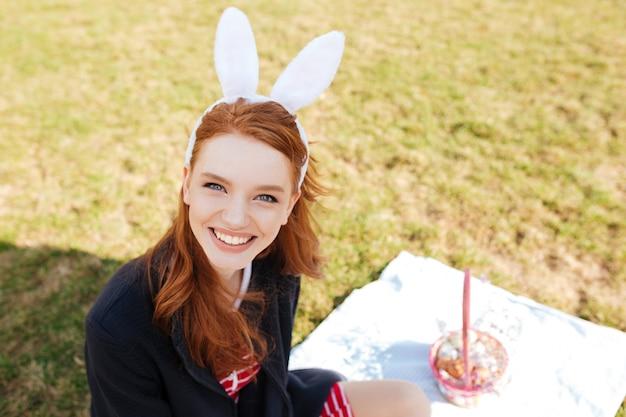 Mujer alegre sonriente con el pelo rojo largo con orejas de conejo