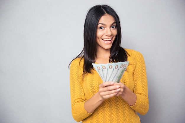 Mujer alegre sosteniendo billetes de un dólar