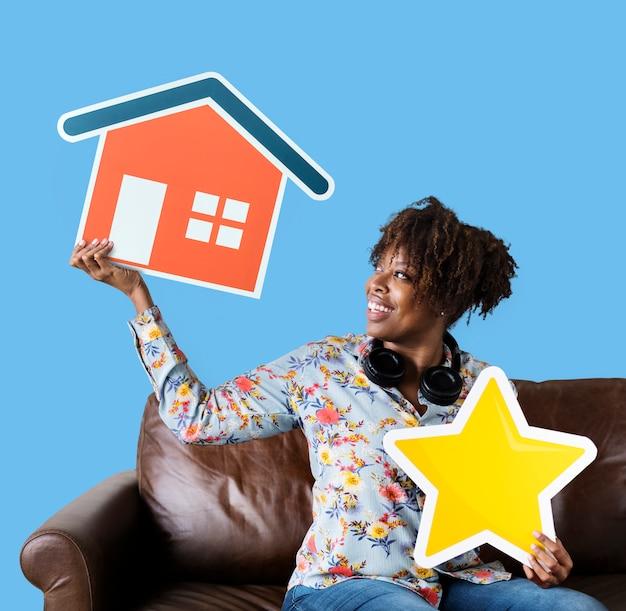 Mujer alegre sosteniendo una casa y estrellas iconos