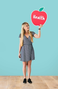 Mujer alegre sosteniendo un icono de manzana saludable