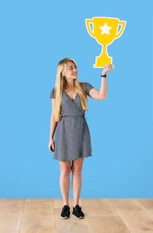Mujer alegre sosteniendo un icono de trofeo