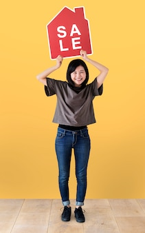 Mujer alegre sosteniendo un icono de ventas de casa