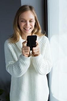 Mujer alegre en suéter blanco con gadget en casa