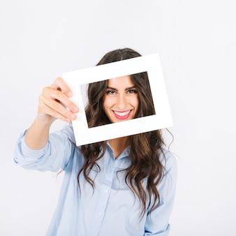 Mujer alegre sujetando marco enfrente de cara