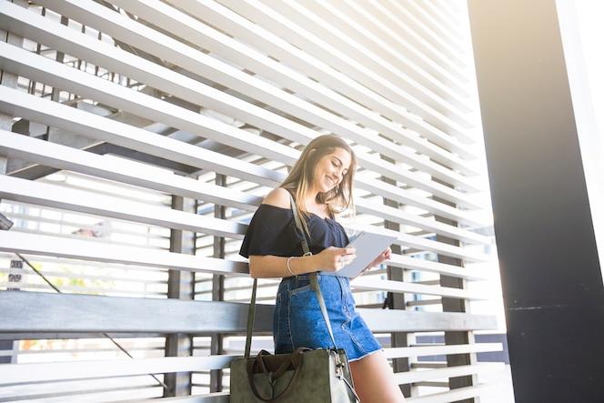 Mujer alegre tableta de navegación cerca de la pared