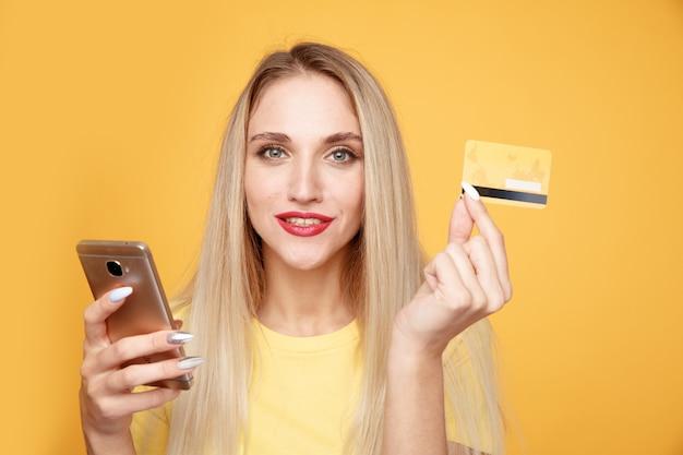Mujer alegre con tarjeta de crédito y teléfono