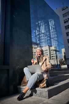Mujer alegre con tarjeta de crédito usando computadoras portátiles para compras en línea