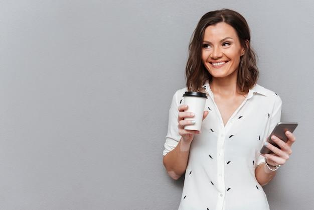 Mujer alegre con taza de café y teléfono inteligente en manos mirando a otro lado en gris