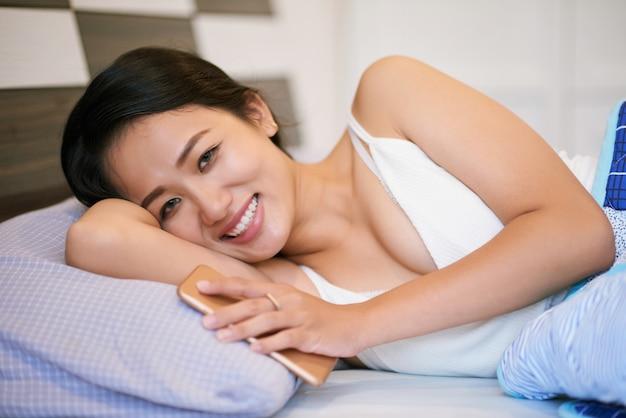 Mujer alegre con teléfono acostado en la cama