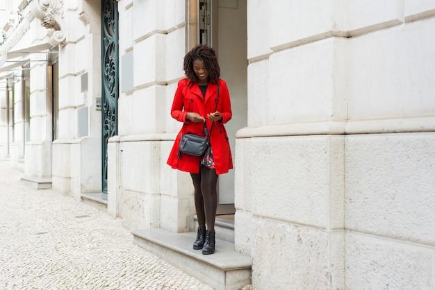 Mujer alegre con teléfono inteligente de pie cerca del edificio