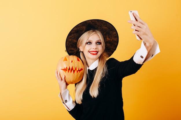 La mujer alegre toma un retrato autofoto contra una calabaza amarilla que se sostiene