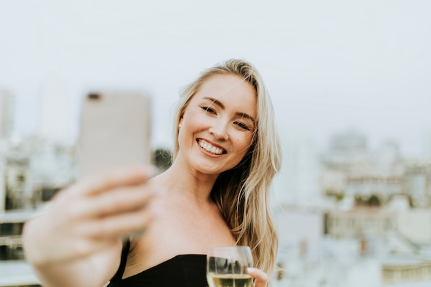 Mujer alegre tomando un selfie en una fiesta en la azotea
