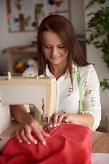 Mujer alegre trabajando en máquina de coser