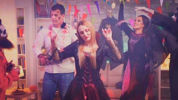 Mujer alegre en traje de repetición sexy para fiesta de halloween. amigos disfrazados.
