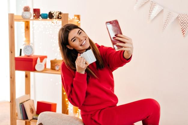Mujer alegre en traje rojo tomando selfie en casa. riendo niña morena bebiendo té en la mañana.