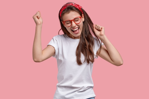 La mujer alegre y triunfante aprieta los puños, se regocija con las noticias positivas, exclama con alegría, modela sobre el espacio rosa