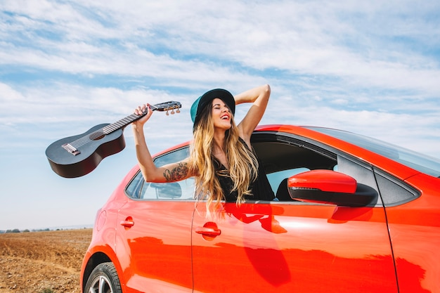 Mujer alegre con ukelele en coche
