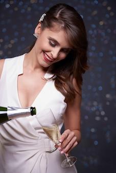 Mujer alegre vertiendo champán en el vaso