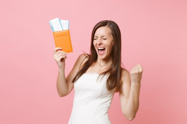 Mujer alegre en vestido blanco haciendo gesto de ganador, sosteniendo el pasaporte y el boleto de embarque, ir al extranjero, vacaciones