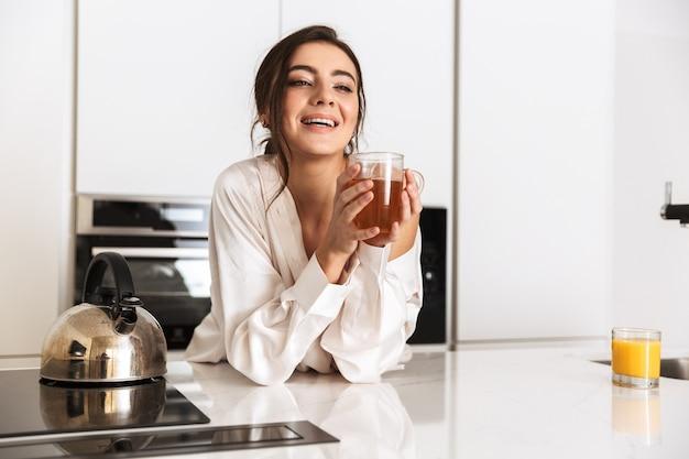 Mujer alegre vistiendo ropa de seda sonriendo, mientras bebe té en la cocina de casa