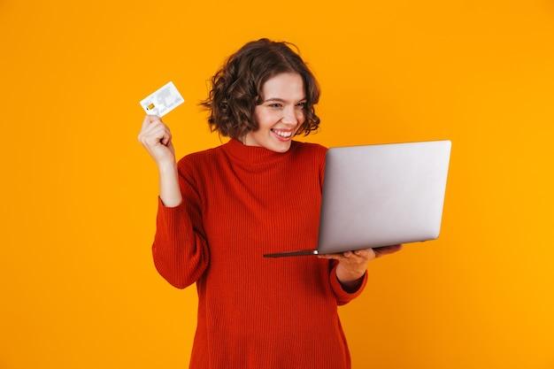 Mujer alegre vistiendo un suéter usando una computadora portátil plateada y una tarjeta de crédito mientras está de pie aislado en amarillo