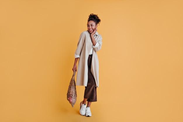 Mujer alegre en zapatillas blancas con bolsa de hilo