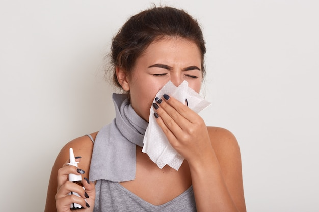 Mujer alérgica enferma sonarse la nariz, tener gripe o resfriarse, estornudar en un pañuelo, posar con los ojos cerrados aislados en blanco, sosteniendo el aerosol nasal en la mano.