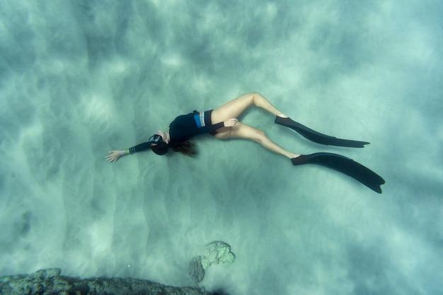 Mujer con aletas nadando en el océano