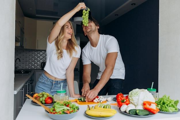 Mujer alimentando a un hombre con uvas durante el hombre cortando un vegetal