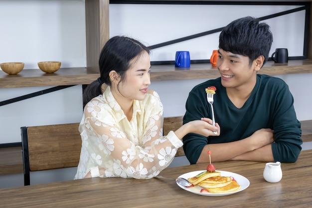 Una mujer está alimentando un pastel de fresa a un hombre.